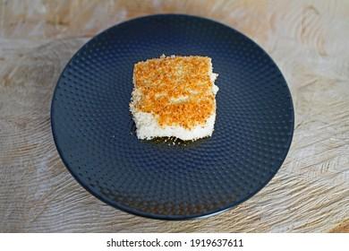 freshly baked coconut buttermilk cake arranged on tree slice