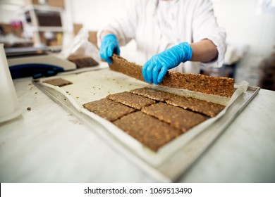 Freshly baked cookie mixture is being cut and getting ready to be packed.
