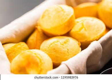 Freshly baked cornbread muffins in basket.
