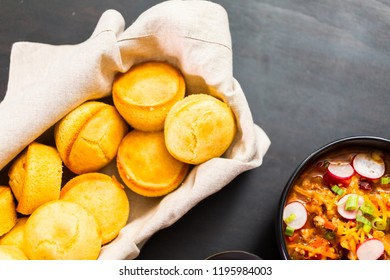 Freshly baked cornbread muffins in basket with turkey chili.