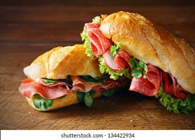 Freshly baked crisp golden baguettes filled with ham and basil or lettuce and salami on a wooden surface