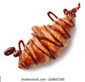 freshly baked croissant decorated with chocolate sauce isolated on white background, top view