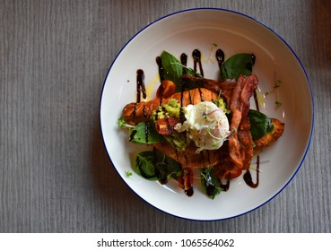 Freshly baked Croissant served with fried bacon, rocket salad, tomato, egg, and balsamic dressing, a delicious breakfast
