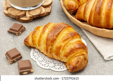 Freshly baked croissants with coffee on a gray background. Delicious and fragrant breakfast.