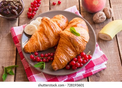 Freshly baked croissants with fruit and nuts
