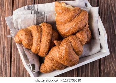 freshly baked croissants on wooden table