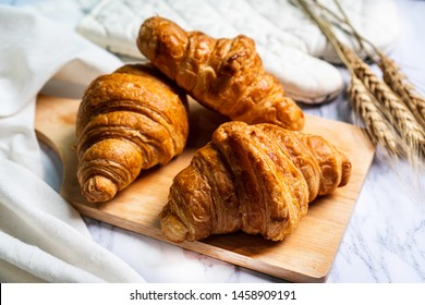 freshly baked croissants on wooden cutting board.