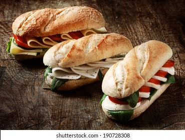 Freshly baked crusty golden vegetarian baguettes in a bakery with a variety of cheese, herb and salad fillings on a rustic wood background, closeup view