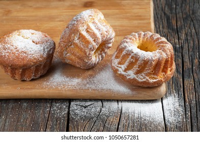 Freshly baked cupcakes sprinkled with powdered sugar on cutting board on the wooden table
