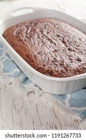 Freshly baked dark chocolate cake in a white pan