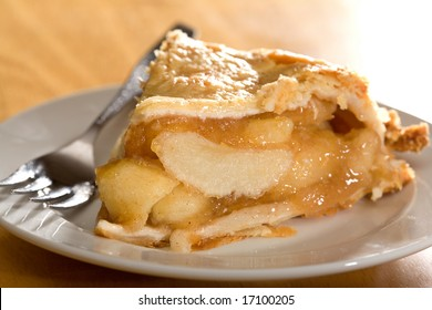 Freshly baked deep dish apple pie served on white plate.