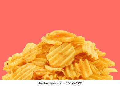 freshly baked deep ridged potato chips on a pink background