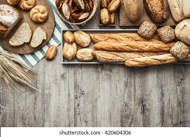 Freshly baked delicious bread on a rustic wooden worktop with copy space, healthy eating concept, flat lay