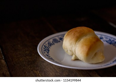Freshly baked dinner roll on a white plate on a dark wooden background