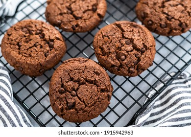 Des biscuits à deux puces de chocolat fraîchement cuits sur un rack de refroidissement.