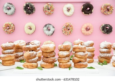 Freshly baked doughnuts in composition on pink wall.