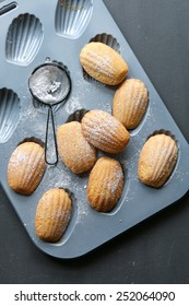 Freshly baked french madeleines on a pan.Top view