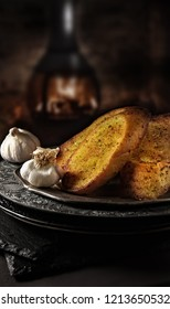 Freshly baked garlic bread slices shot against a dark rustic background with a roaring traditional wood burner in the background. The perfect image for your bistro or restaurant menu cover art.