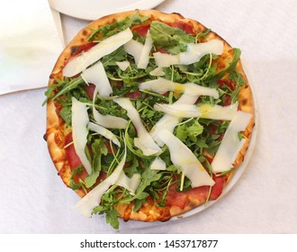 Freshly baked gluten free pizza with ham and parmesan