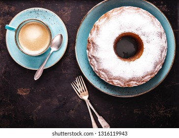 freshly baked gugelhupf with a cup of coffee crema on a dark background, top view