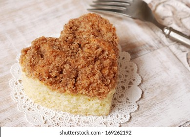 Freshly baked heart shaped cinnamon coffee cake on rustic wooden tray with vintage fork.