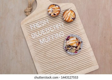 """Freshly baked homemade blueberry muffins on a letterboard that says """"fresh blueberry muffins.""""  Letterboard is shapped like a cutting board."""
