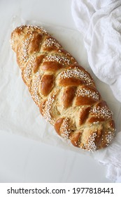 Freshly baked homemade braided challah bread for Shabbat and Holidays, top view, white background, copy space
