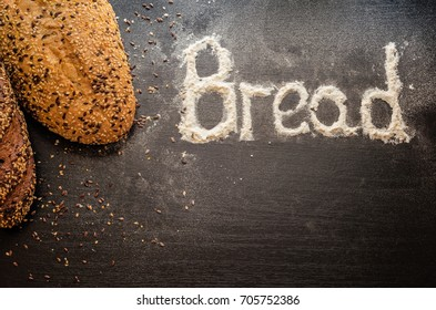 Freshly baked homemade bread with different seeds on a dark wooden background. Baking flour spilled on the table. The text from the flour: Bread. Different loaves of bread to choose.