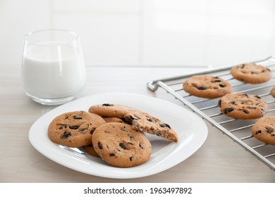 Freshly baked homemade chocolate chip cookies in white plate and on cooling rack with glass of milk on wooden kitchen table. Recipe of cookies with chocolate chips just from oven for lunch treat.