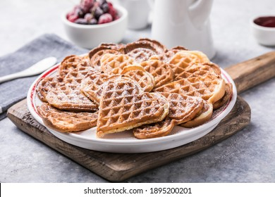 Freshly baked homemade heart shaped Belgium waffles  on gray background. European baked pastry sweets.  St. Valentine's Day breakfast concept.