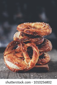 Freshly baked homemade soft pretzel with salt on rustic wooden table. Retro toned image.