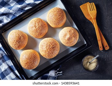 Freshly baked hot homemade burger buns sprinkled with sesame seeds on a baking pan, view from above, flat lay