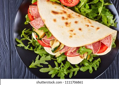 freshly baked italian piadina with mozzarella, tomato, salami slices, grilled zucchini and arugula on a black slate plate on a black wooden table, view from above, close-up, flat lay