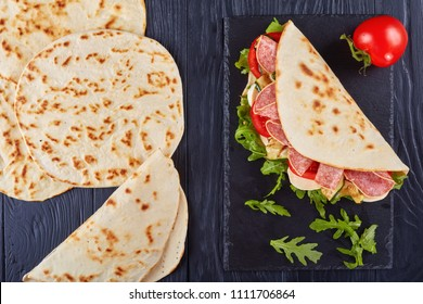 freshly baked italian piadina with mozzarella, tomato, salami slices, grilled zucchini and arugula on a black slate plate on a wooden table, view from above, flat lay