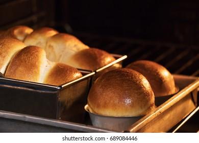 Freshly baked loaf of brioche bread in oven. Homemade bakery. Making brioche bread.