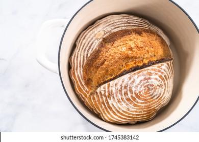 Pain fraîchement cuit d'un pain de pâte de blé avec des marques de panier d'imperméabilité au pain dans un four émaillé en fonte de fer.
