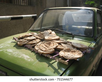 Freshly baked loaves of Egyptian flatbread for sale on the front of a green car on a street in Cairo, Egypt