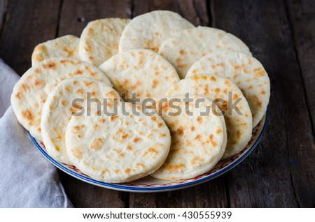 Freshly baked Moroccan mini flatbread - batbouts on wooden table. Selective focus. Arabian food