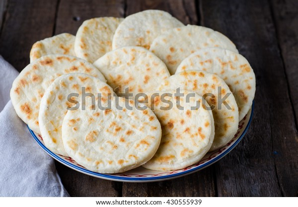 Freshly baked Moroccan mini flatbread - batbouts on wooden table. Selective focus. Arabian food