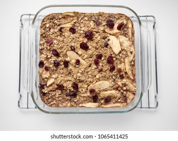 A freshly baked oatmeal with apples, walnuts and dried cranberries in a square glass plan sitting on a cooling rack.