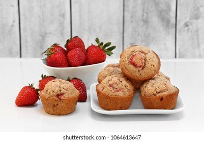 Freshly baked organic strawberry muffins, with whole fresh berries.