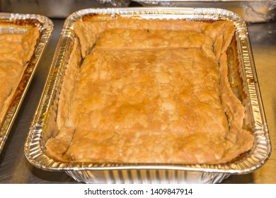 Freshly Baked Peach Cobbler:  Freshly baked peach cobbler in a pan ready to be served at a restaurant deli.