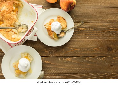 Freshly baked peach cobbler with scoop of whipped cream.