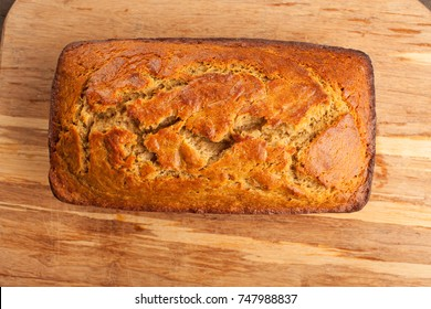Freshly baked pumpkin bread loaf on cutting board with knife on dark wood background top view
