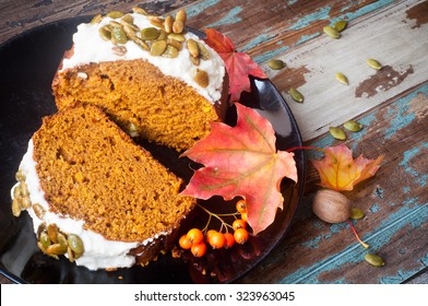 Freshly baked pumpkin loaf cake bread iced with decorated with pumpkin seeds. Served on a rustic wooden table with autumn leaves and berries.