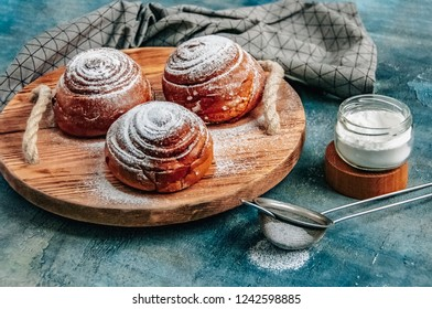 Freshly Baked Rolls with powdered sugar on old background. Sweet danish Cinnabon. Pastry.