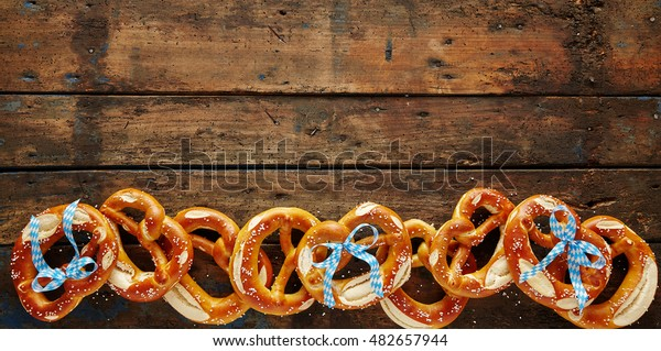 Freshly baked salted Bavarian pretzel banner on old rustic wood in a wide angle view with copy space for Oktoberfest