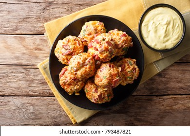 Freshly baked sausage balls with cheese cheddar on a plate and mustard sauce in a bowl close-up. horizontal top view from above