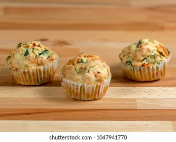Freshly baked savory muffins with cheddar, spinach and bell pepper