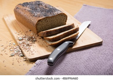 Freshly baked, sliced banting seed loaf or paleo bread on a board with bread knife and seeds
